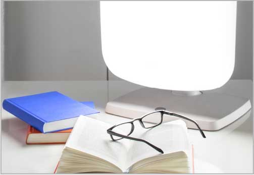 Therapy light sitting on desk with books