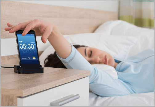 Woman in bed reaches for phone alarm on nightstand