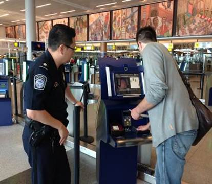 A police officer assisting a passengar at an airport self check-in.