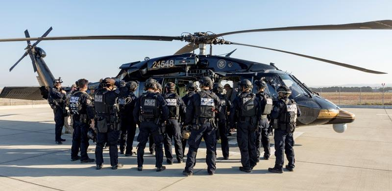 DHS officers in front of a CBP helicopter