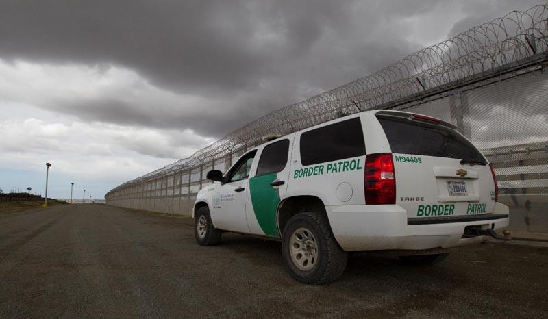 Border Patrol vehicle next to a fence