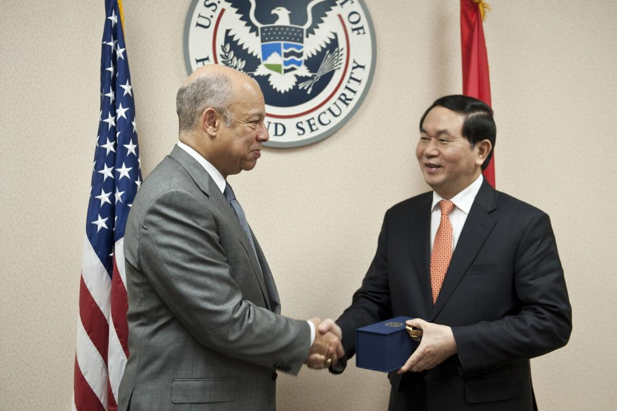 Secretary Johnson, Minister Tran Dai Quang shake hands in front of DHS seal
