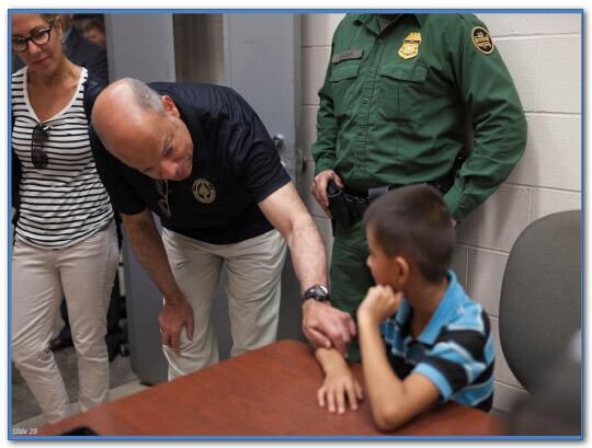 Secretary Johnson speaks with a boy being held by Customs and Border Protection