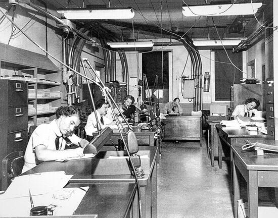 After a WAVE completed a run on her bombe (which took 20 minutes) she gave her print out to her supervisor for verification. The supervisor then took the results to the Watch Office for logging. The verified and logged results were sent via a pneumatic tube system to the cryptanalysts located in Building 2. (National Archives and Records Administration)