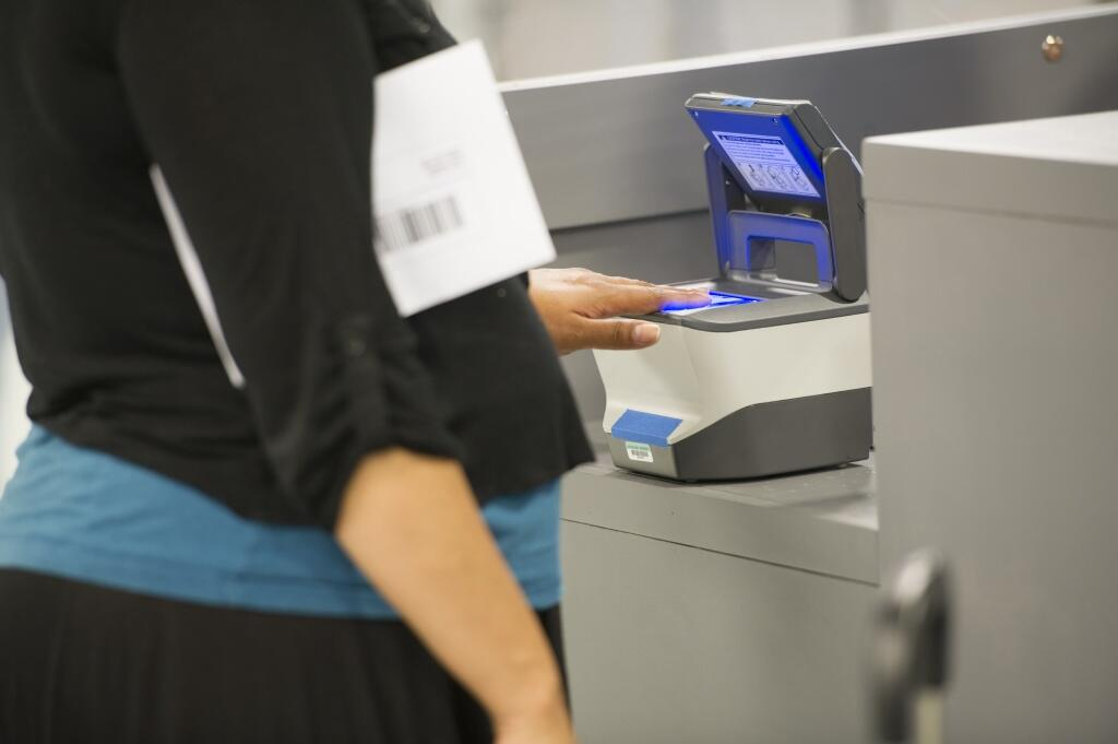 A woman allows a biometric device to scan her fingerprints.