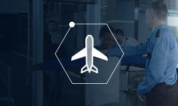Icon of an airplane in a honeycomb shape over a blue screened photo of person working at an airport.