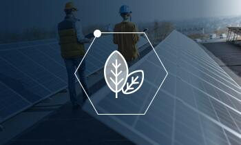 Icon of two leaves in a honeycomb shape over a blue screened photo of people working with solar panels.