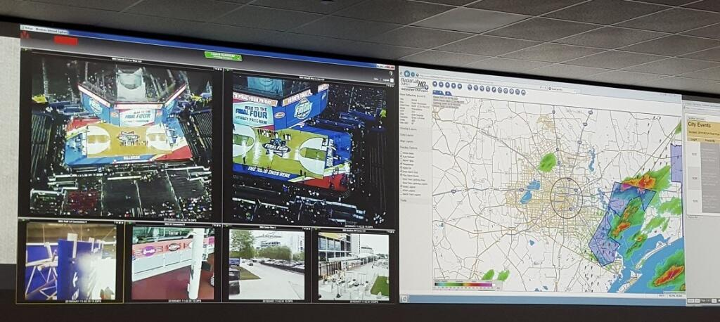 A screen divided into smaller screens displaying different inside and outside areas of a sports arena on the left and a map on the right.