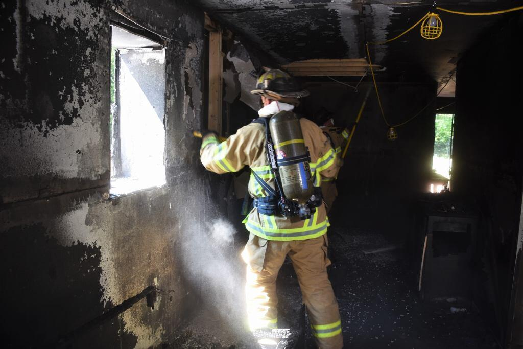 Firefighter in overhaul environment with skin exposed to toxic combustion products.