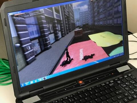 Close up shot of a laptop running an EDGE virtual training scenario. The screen depicts the medical triage area on the street outside of the hotel