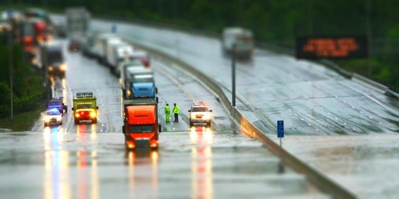First responders direct traffic on a flooded highway.