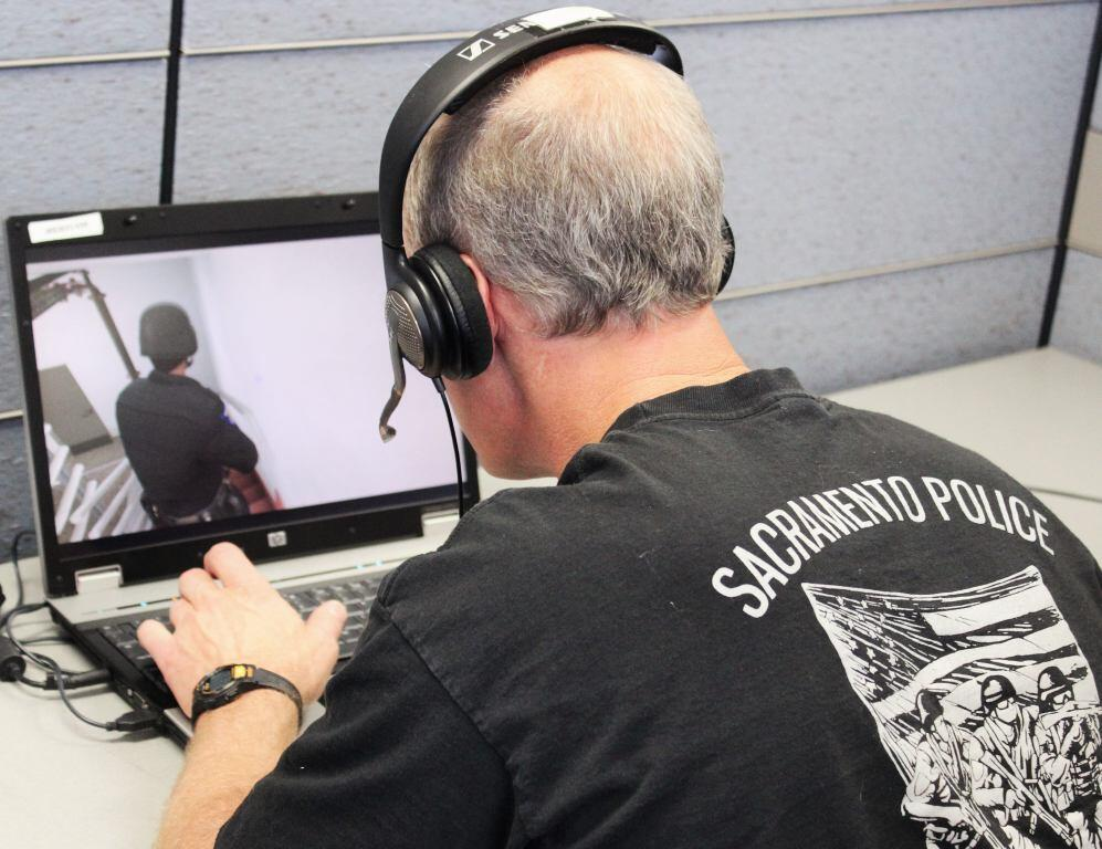 Actual law enforcement officer uses a laptop to command an avatar during a 2013 exercise in Sacramento, California, where EDGE was piloted.