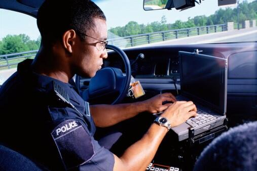 A police officer sits in his car typing on a laptop
