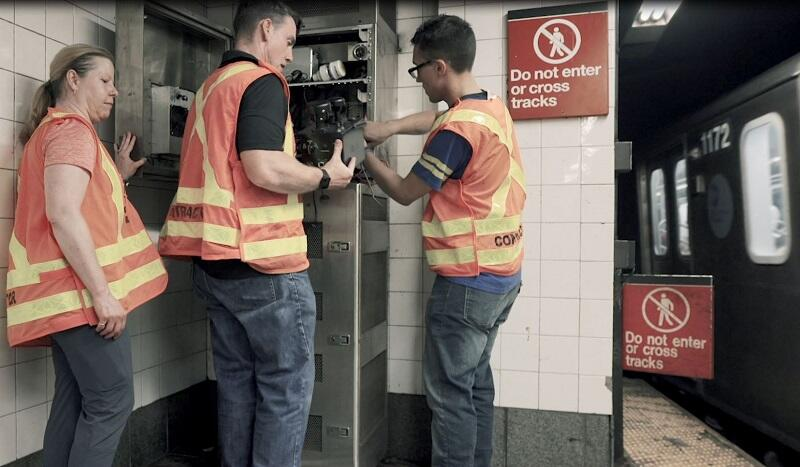 MIT Lincoln Laboratory personnel install support equipment in one of the testbed cabinets in the NYC subway.