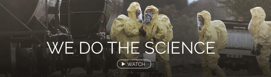 We Do the Science. Watch. People wearing hazmat suits at an industrial site.