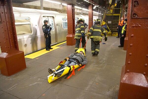 First Responders use a medical skid to evacuate a passenger on passenger from the metro.
