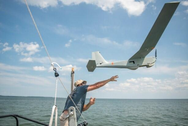 A man on a boat floating over water launches a drone by tossing it in the air.