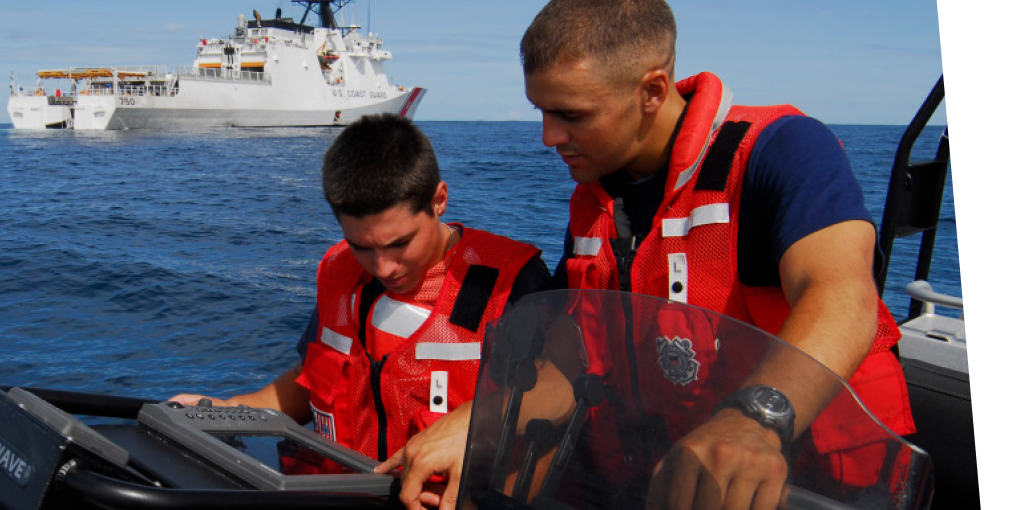 Agents on a boat using a hand held technology.