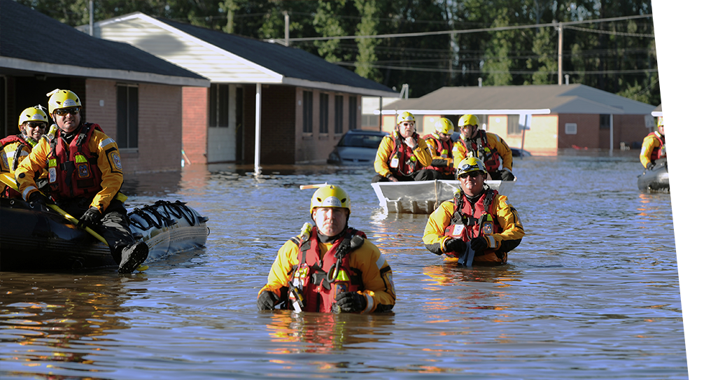 Emergency responders in high flood water rescuing people.