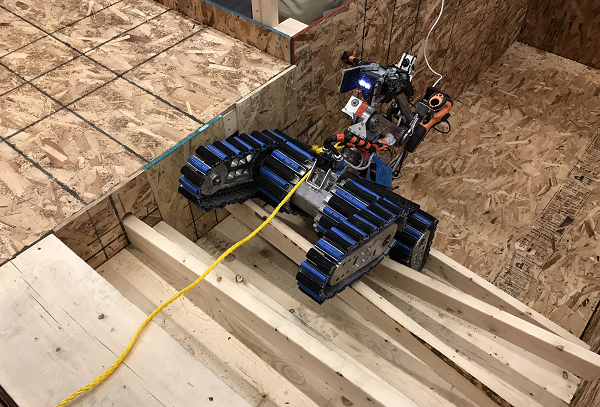 A robot trudges up a set of stairs, one of the test methods developed by S&T and NIST. Robot mobility was tested at three levels of difficulty, the height of which is said to be comparable to wall-climbing.