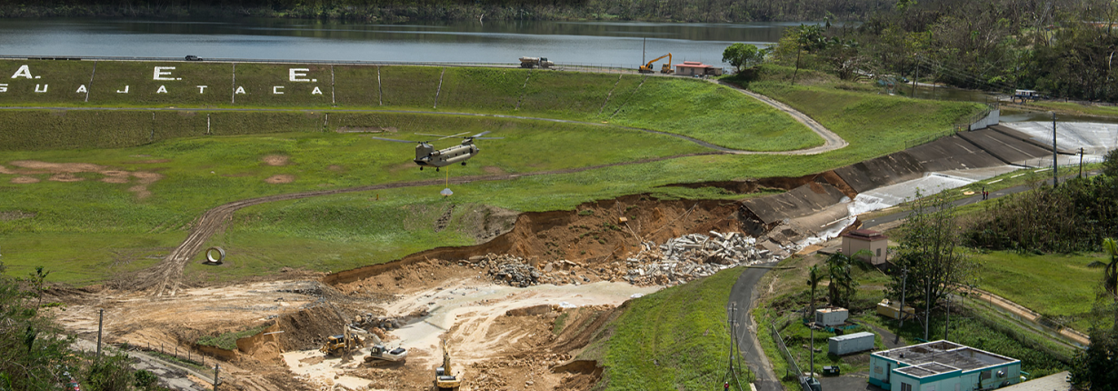 A helicopter of the U.S. Army Corps of Engineers brings sandbags full of crushed rock to stabilize the damaged spillway of the Guajataca Dam, Puerto Rico after Hurricane Maria.