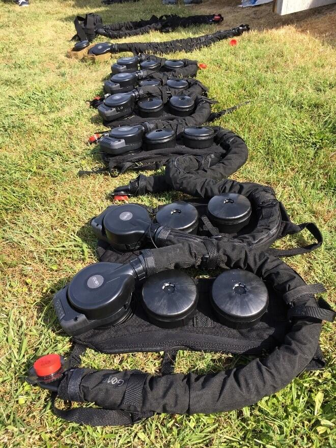 PAPRs lay on the grass before the test at MSRT East in Chesapeake, Virginia. The filters and air hoses are worn as backpacks. Photo by Don Bansleben, S&T.
