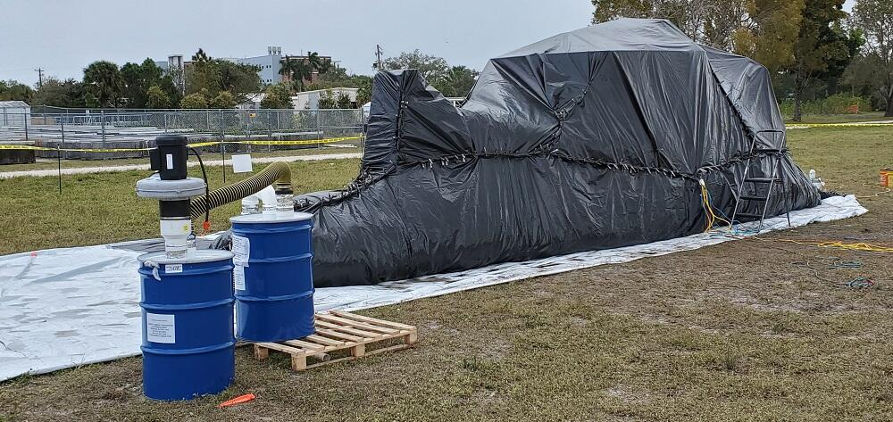 Participants wrapped the boat in plastic during the decontamination process. On the left are the barrels with activated carbon where methyl bromide is captured after the decontamination step.