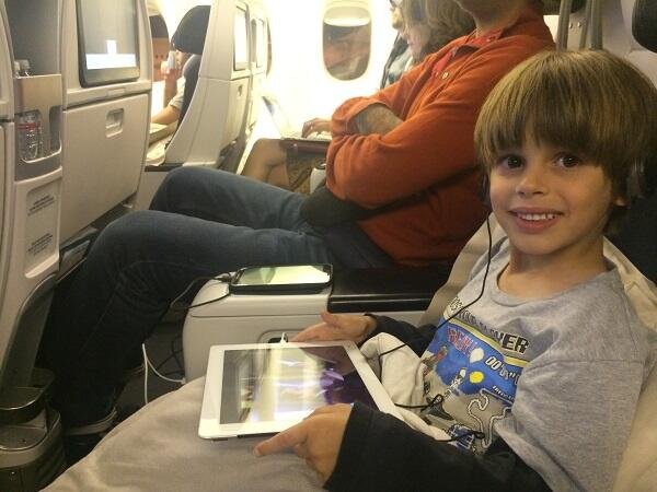 Child sitting in an airplane seat with an iPad