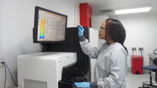 A molecular biologist at the NBACC forensic laboratory examines a DNA sample in front of the Illumina HiSeq high capacity DNA sequencing instrument.