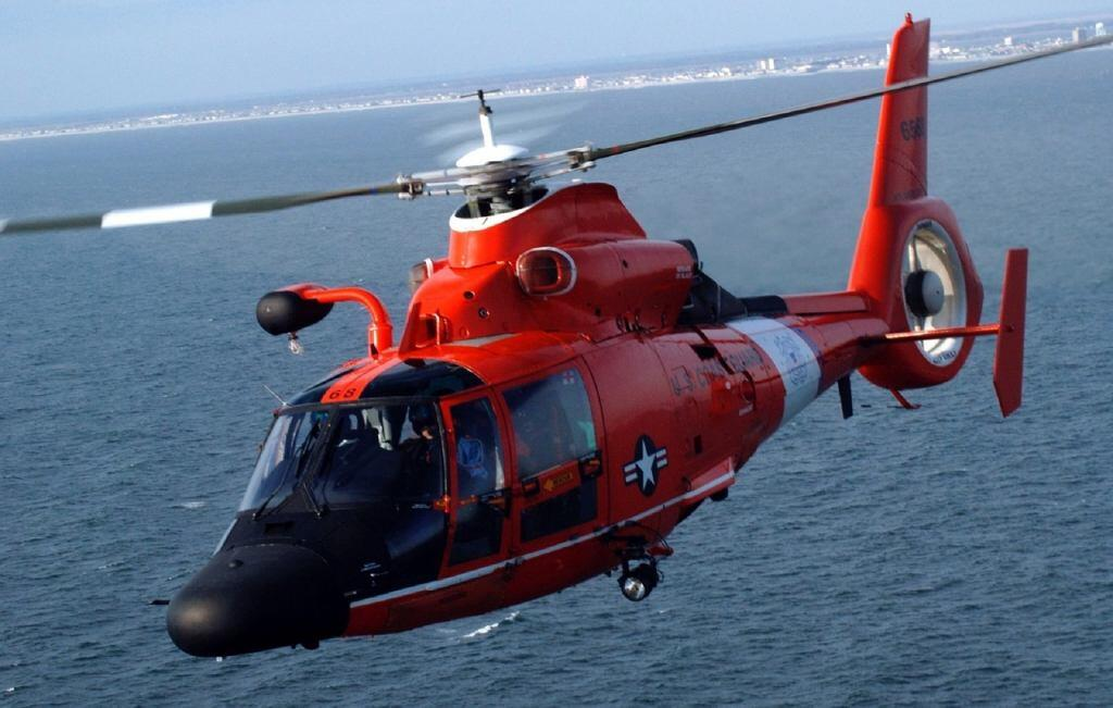 Coast Guard helicopter flying over water.