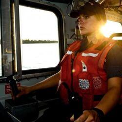 Member of the United States Coast Guard pilots a boat.