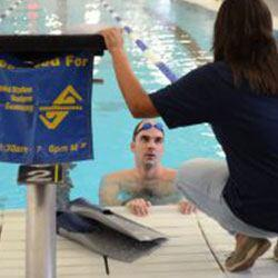 Petty Officer 1st Class Robert Troha talks to Gianna Davis, a U.S. Masters Swimming coach, during training at George Block Aquatics in San Antonio. (Photo by Petty Officer 2nd Class Grant DeVuyst)
