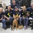 "A team of canine search specialists from Nebraska Task Force 1 wait in their dorm room of sleeping bags, cots and crates at the Base of Operations in Katy, Texas before being deployed on an urban search and rescue mission. Team members pictured from left to right are: Dwayne Koranda, Steve MacDonald, Levi Holte, Andrew Pticher (with golden retriever ""Chief""), Rhonda Stuhrenberg (with Belgian Malinois ""Sig""), and Damon Wirth (with black Labrador retriever ""George""). FEMA supports federal agencies, the state,"