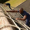Recruit climbing the cargo net obstacle.