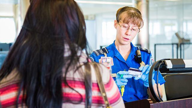 TSA Agent looking at a traveler's driver's license.