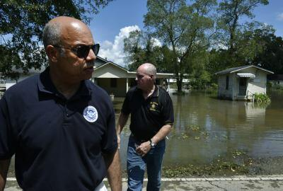 Secretary Johnson walks up the bank of a flooded road
