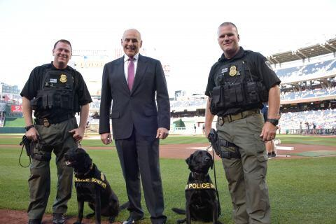 "Secretary Kelly stands with DHS K-9 teams Dennis Tyree and ""Coal"" and Scott Eschelman and ""Judge"". DHS K-9 teams are responsible for the safety and security of DHS headquarters and the constant flow of personnel in and out of the facility. (Jetta Disco/DHS)"