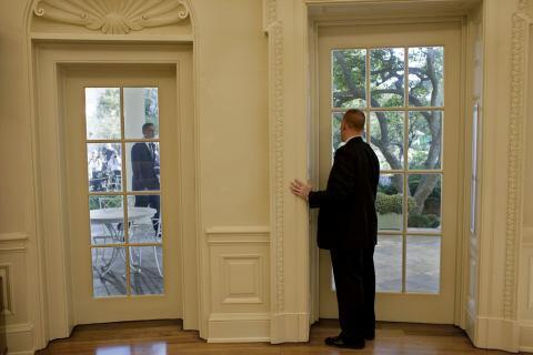 A U.S. Secret Service agent prepares to open the door to the Oval Office for President Barack Obama.