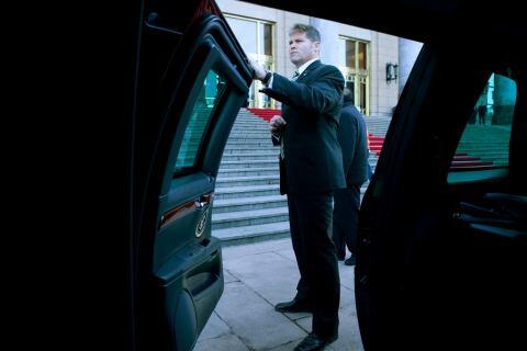 A U.S. Secret Service agent waits by the spare limousine