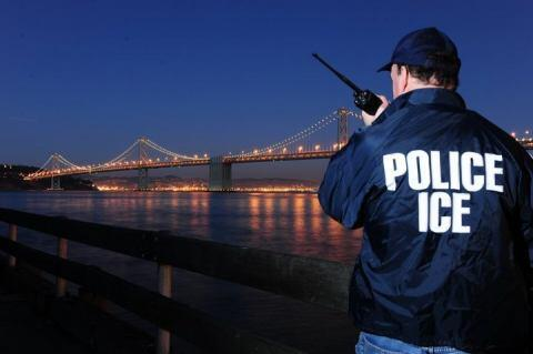 An ICE agent conducts surveillance work at dusk near the San Francisco – Oakland Bay Bridge.