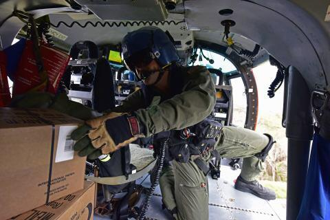 Coast Guard Petty Officer 2nd Class Guy Walkner, flight mechanic, drops food and water to victims of Hurricane Maria near La Estancita, Puerto Rico, from a Coast Guard Air Station Borinquen MH-65 Dolphin helicopter on Oct. 5, 2017. Air Station Borinquen has been helping deliver food and water to people stranded by mudslides and washed out roads. (U.S. Coast Guard photo by Petty Officer 3rd Class Eric D. Woodall)