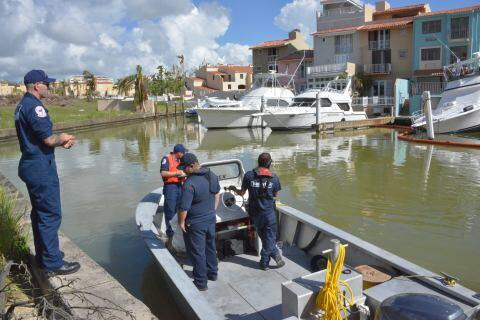 U.S. Coast Guard Petty Officer 1st Class John Newcomer, the assistant safety officer, speaks with Petty Officer 1st Class Jason Pronovost before he places response stickers to identify sunken vessels caused by Hurricane Maria in Culebra, Puerto Rico, Oct. 31, 2017.  The Maria ESF-10 PR Unified Command, consisting of the Department of Natural and Environmental Resources, U.S. Coast Guard in conjunction with the Puerto Rico Environmental Quality Control Board, Environmental Protection Agency and the U.S. and