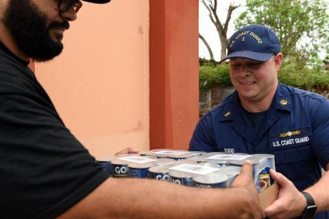 U.S. Coast Guard Chief Warrant Officer Brandon Todd passes supplies to a local missionary in Loiza, Puerto Rico, on November 8, 2017. The crews worked together to provide disaster relief supplies, food and water to the victims of Hurricane Maria. U.S. Coast Guard photo by Petty Officer 2nd Class Ali Flockerzi.