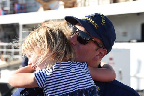 Petty Officer 2nd Class Ryan Steiger, a crewmember aboard the Coast Guard Cutter Venturous, kisses his daughter, 3-year-old Lily Steiger, after returning home to St. Petersburg, Florida, Nov. 13, 2017. The Venturous and it's crew returned to homeport after a 69-day patrol conducting hurricane relief and law enforcement operations in the Caribbean Sea. (U.S. Coast Guard photo by Petty Officer 2nd Class Ashley J. Johnson.)
