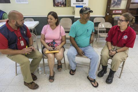 Refugio, Texas, September 8, 2017 – Disaster survivors Susanne Lara (center left) and Daniel Porras (center right) receive registration assistance following Hurricane Harvey from Brandon Whitman (left), FEMA Disaster Survivor Assistance (DSA) Specialist, and Kimberly Aufrecht (right), FEMA Corps Team Lead, at Refugio City Hall. FEMA supports federal agencies, the state, local communities, counties, volunteer agencies active in disaster and tribal entities in providing assistance to disaster survivors. Photo