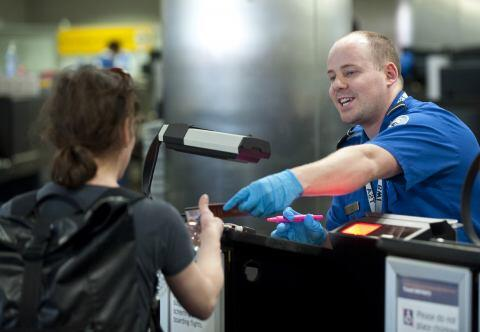 A TSA agent checks a passenger's identification before allowing them to proceed through security