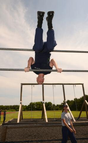 Recruit flipping over an obstacle on the confidence course.