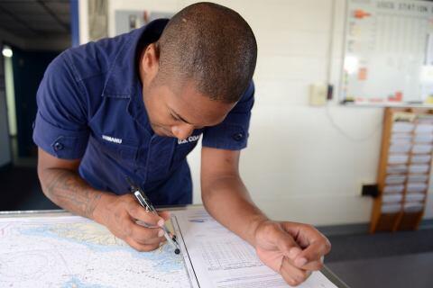 Coast Guard Fireman plots a position on nautical chart.
