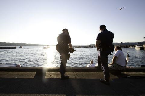 Security team members talk with locals on a pier.