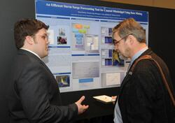 Award-winning student researcher Bryan Herring describes his study on forecasting storm surges and flooding to an attendee at the DHS University Network Summit.